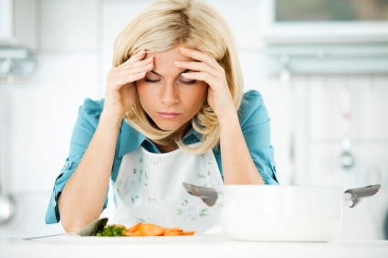 Young blonde housewife having a headache while preparing dinner.